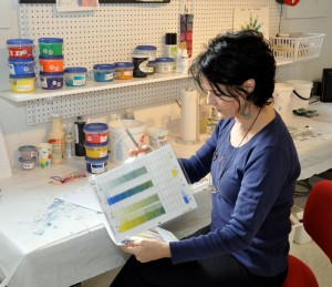 Artist Shirley Williams studying color tests and swatches.