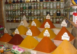 Piles of colorful yellow and orange spices in a Moroccan shop.