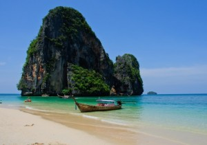 Large rock off the coast of Phra Nang Beach, Thailand, surrounded by deep blue skies and sea.