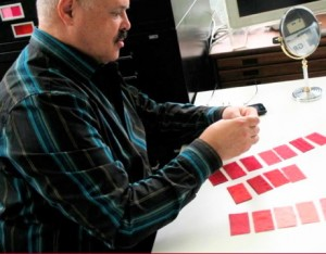 Personal Style Counselor John Kitchener holds up pink Munsell color swatches