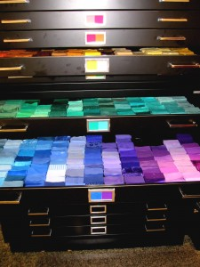 A black filing cabinets with draws opened to show swatches of Munsell color coded fabrics