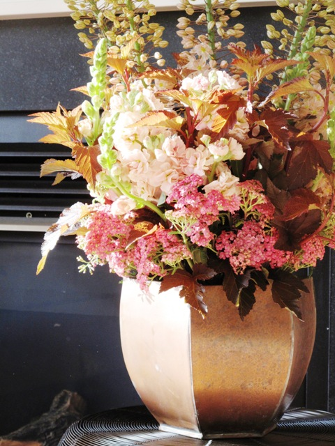 An arrangement of pale colored flowers in a coppery vase
