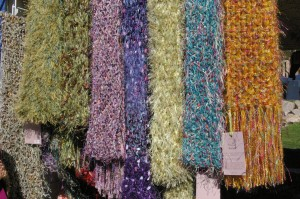 A selection of beautifully hand knitted colored scarves at the Blackberry Bear booth at the Fountain Hills art and craft show.