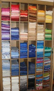 Quilter Maria Elkins' shelves of fabric - a palette of fabric arranged in color wheel order.