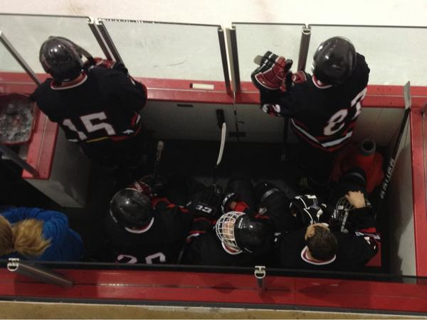 UC Bearcat Hockey skaters in the penalty box wearing black