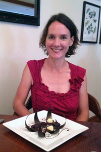 A smiling Kathryn Sampeck sitting in front of a plate of different colored chocolates