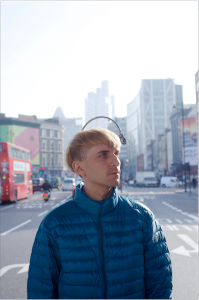 Neil Harbisson, who hears sound through a camera attached to an antenna on his head, standing in a city street.