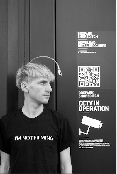 "Neil Harbisson, who hears sound through a camera attached to an antenna on his head, wearing a t-shirt saying ""I'm not filming""."