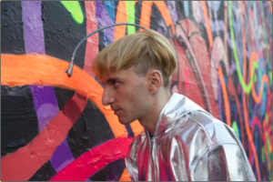 Neil Harbisson pointing the camera attached to his head at a wall mural painting to hear the sounds of the colors.