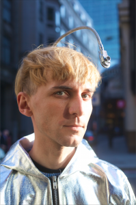Neil Harbisson, color blind cyborg who hears colors, dressed in silver jacket.