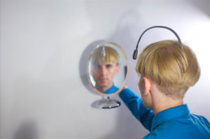 Neil Harbisson, a color blind cyborg who hears colors, viewing himself in a mirror.