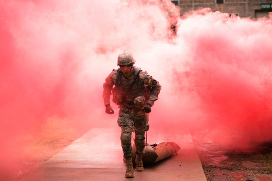 A soldier running out of a plume of red smoke obscuring what is behind him