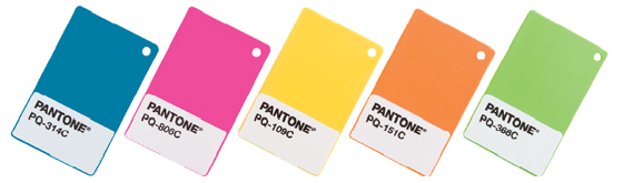 A row of Pantone plastic color standard chips in blue, pink, yellow, orange and green