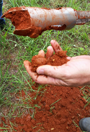 An archaeologist holds a pile of Marsala colored soil from an excavation