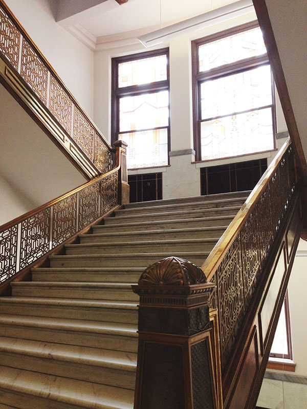 A grand stairwell at the old Colorado Museum with light beaming through the windows