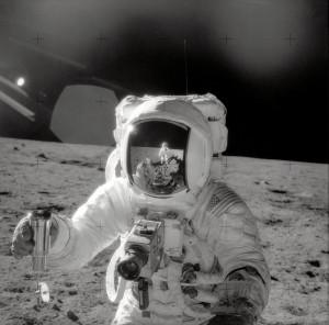 Apollo 12 astronaut Alan Bean on the moon with a lunar soil sample.