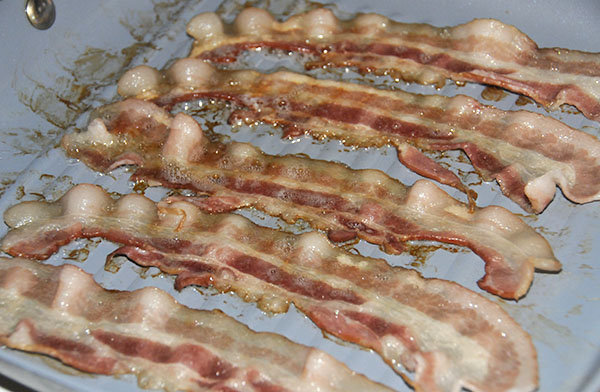 Bacon in a pan showing the color of still chewy bacon