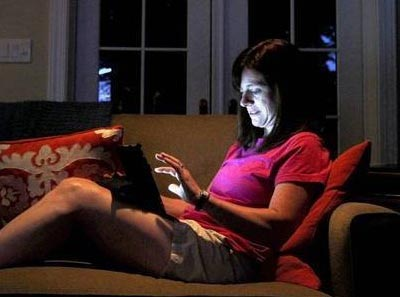 A women sitting on a couch on her laptop, blue light emitting from the screen