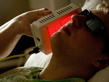A young man using red light therapy to treat skin conditions