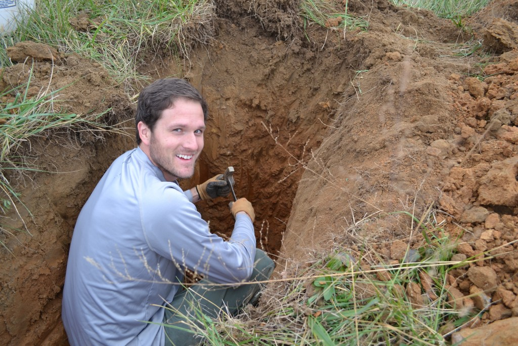 "Ernest ""Bubba"" Beasley, MS, CPG - Geologist, examining soil in a backhoe pit."