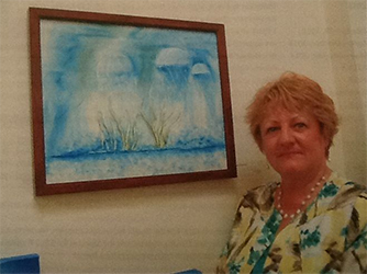 A photograph of artist Iris Hardy standing next to one of her paintings