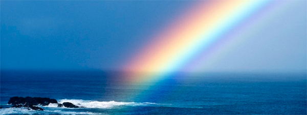 A bright rainbow over the blue ocean and sky