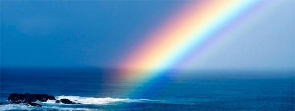 A bright rainbow over the blue ocean and sky