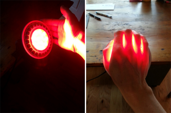 A deep penetrating red light shinning on and through a persons hand