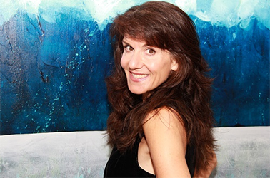 A portrait of artist and color therapy expert Leanne Venier in front of one of her blue and white paintings