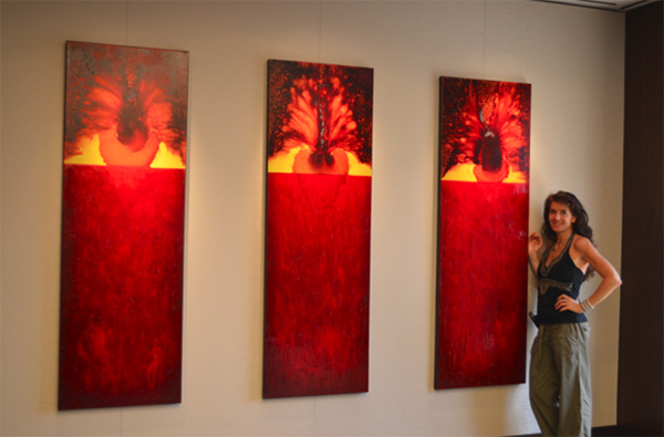 Leanne Venier standing in front of a triptych of paintings in red
