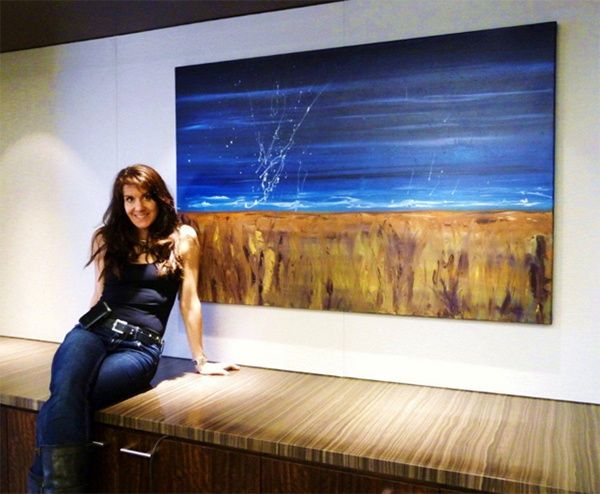 Leanne Venier sitting in front of one of her paintings