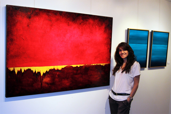 Leanne Venier standing in front of her paintings, one in red and a diptych in blue
