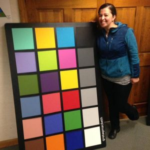 Laura Weeks, lab technician at Munsell stands next to a full size ColorChecker chart