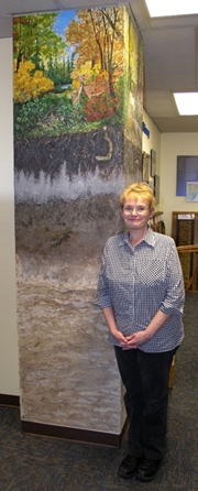 A photo of Janis Lang in front of one of her Lewis & Clark soil paintings