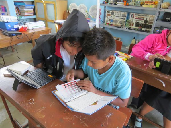 Students in Nivin, Peru, learning to use the Munsell Color Book to record data from ceramic sherds curated in the museum at their school.