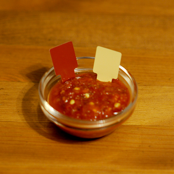 A glass jar filled with hot sauce showing Munsell color notation