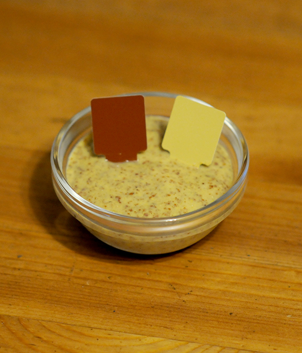 A glass jar filled with mustard showing the Munsell color notation