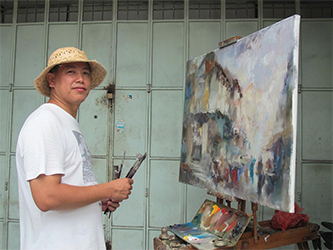 Ng Woon Lam turns to smile at the camera while working on a painting