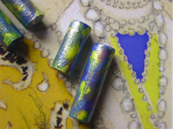 Paper beads site on top of the painting they are made from