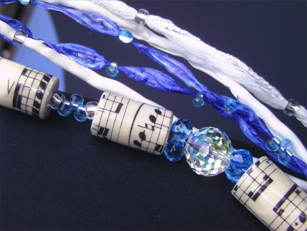 Another view of a necklace made with blue beads, paper beads from a 1900's score and Swarovski crystals.