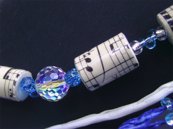 A necklace made with blue beads and a score from the 1900's to create the paper beads with Swarovski crystals