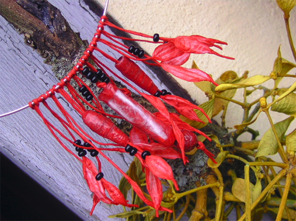 A necklace with red peppers hanging from strings inspired by mistletoes and green peppers
