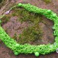 A bright green necklace with woven circles of paper and hanging beads sits on soil
