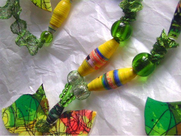 A green and yellow necklace made from paper beads and flower-like leaves