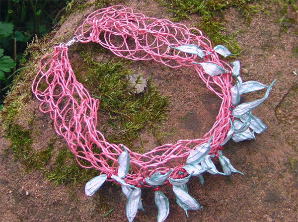 A pink woven paper necklace with purplish petals