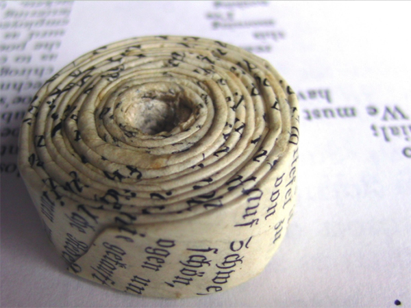 Old paper that has been curled up into a roll shows it yellowing with age