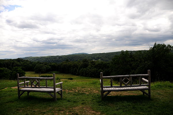 Two wooden benches amidst a stunning view of the Hudson Valley at the FDR home in Hyde Park