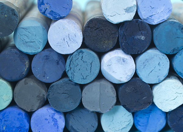 A pile of blue crayons in different value and chroma