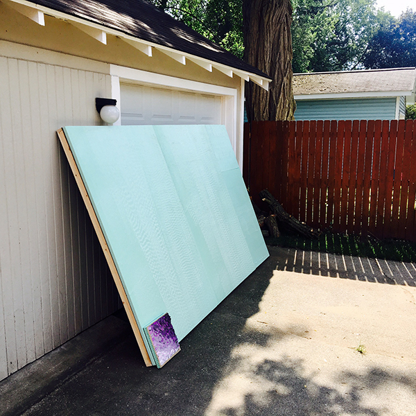 A large wood panel rests against a garage door ready for color chips