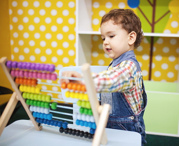 A young boy plays with a colorful counting toy